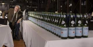 Francis Schott, co-owner of Catherine Lombardi and Stage Left restaurants in New Brunswick, sits next to the rows of bottles he